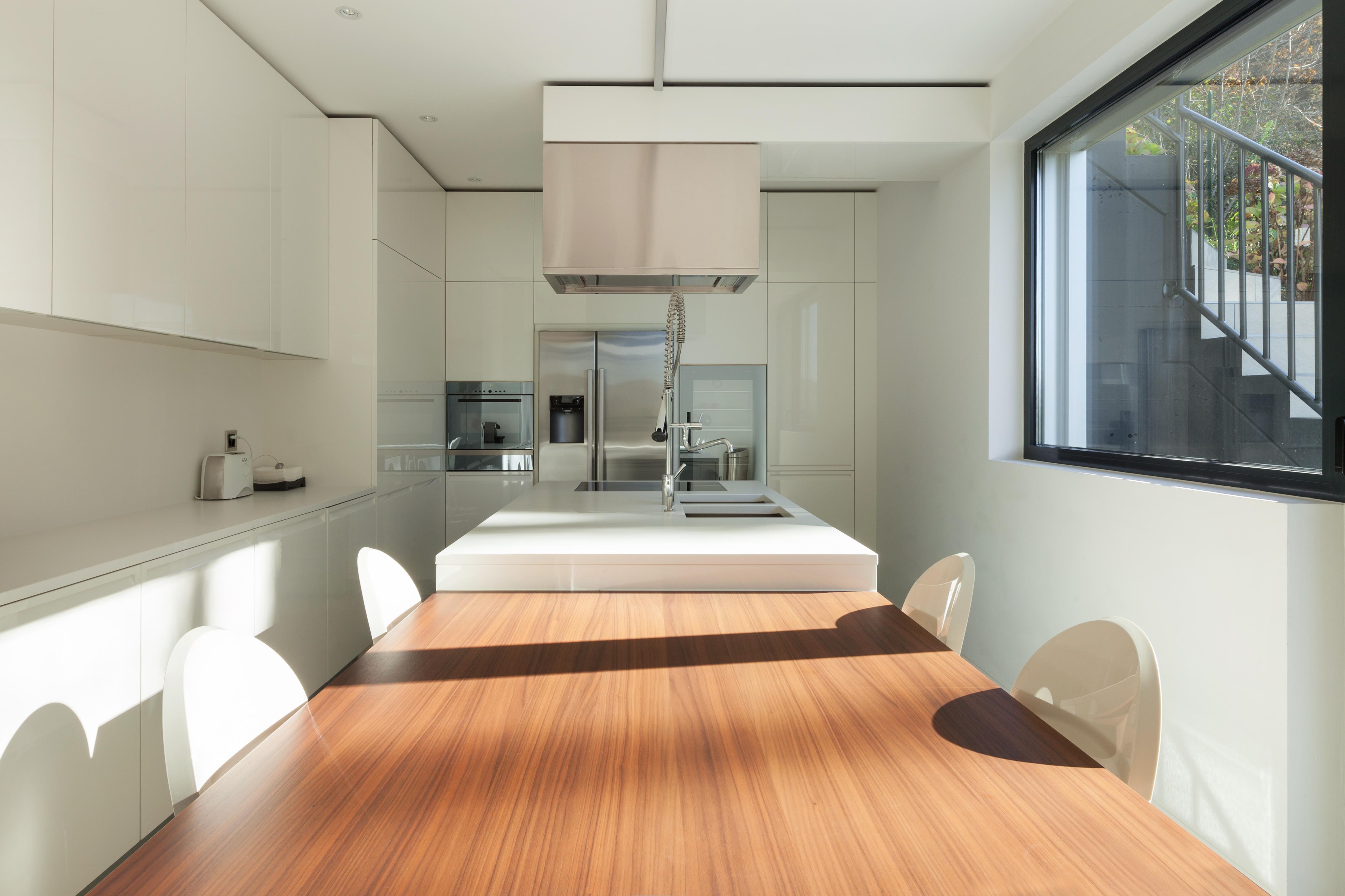 cozinha estrieta com móveis brancos e mesa de refeições