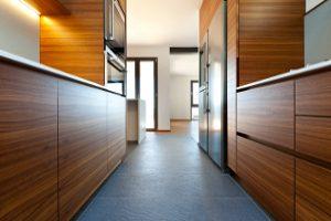 cozinha muito estreira com móveis dos 2 lados