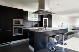 Cozinha com móveis pretos e com ilha